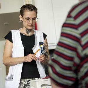 Lähihoitaja Nicole Fagerberg antaa kotihoidon asiakkaalle päivän insuliiniannoksen kesällä 2019