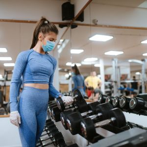 En kvinna i munskydd lyfter upp vikter på ett gym.