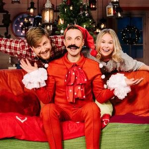 En tomte poserar med två människor vid en soffa.