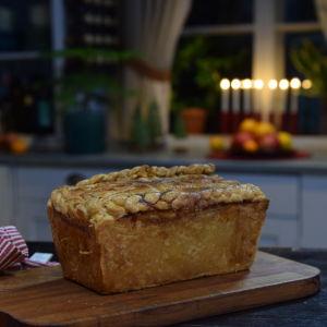 Smördegsinbakad paté på en skärbräda i ett kök