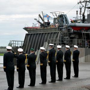 Flera militärer står på rad och tittar på när den finska flaggan hissas på ett militärfartyg.