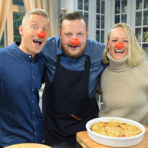 Kaksi miestä ja nainen punaiset pellenenät nenällään hymyilevät keittiössä omenapiiraan äärellä.