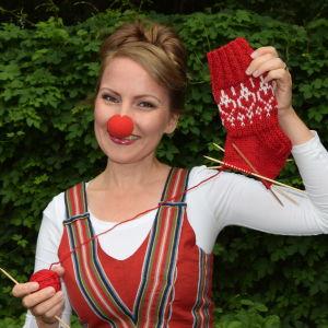 Kvinna med clownnäsa håller upp halvföärdigt stickad socka