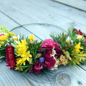 En blomsterkrans som bundits på en grov metalltråd och som bara har dekorerats i en halvcirkel. Växterna som använts ör röd nejlika, gul allium, prästkrage och tallris med späda gröna kottar.