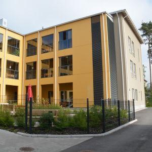 Ett gult hus på en innegård som är Villa Anemone, ett äldreserviceboende i Karis.