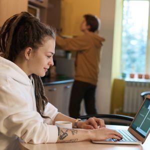 Kvinna i ponnysvans och vit luvtröja sitter vid köksbord och läser på sin bärbara dator. I bakgrunden ett fönster och en man som tar ut något ur ett kylskåp.