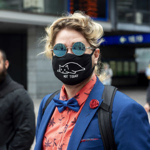 Person som bär ett svart ansiktsskydd i stadsvimlet.