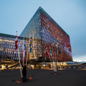 Nordiska flaggor hissas utanför kulturhuset Harpa i Reykjavik i kvällsbelysning.