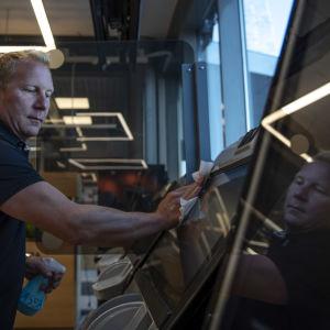 K-supermarket Mustapekan kauppias Jouni Ekholm pyyhkii peliautomaatteja ensimmäisiä asiakkaita varten koronakevään jälkeen.
