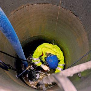 Kypäräpäinen mies puhdistaa juomavesikaivoa.