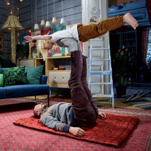 En man ligger på marken med benet uppe och en pojke leker flygplan på foten.