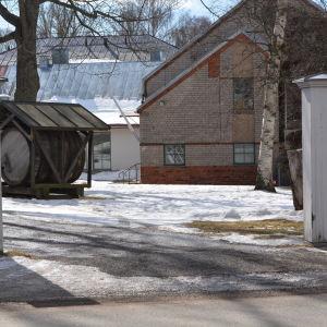 En snöig gård syns genom en port.