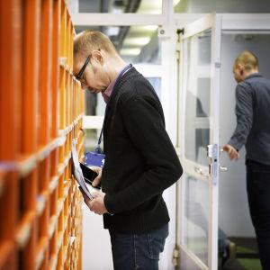 Työntekijä nojaa otsallansa työpaikan postilokerikkoihin.