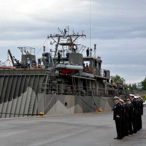 Flera militärer står på rad vid ett militärfartyg.