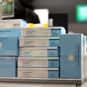 Kasvosuojainpaketteja kasattuna päällekkäin apteekissa.