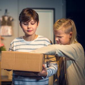 En pojke och en flicka i bild. Pojken hållern papplåda i händerna, flickan har ena handen inne i lådan.