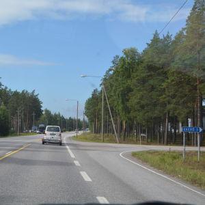 En T-korsning, asfaltvägar, några bilar syns. Sommar.
