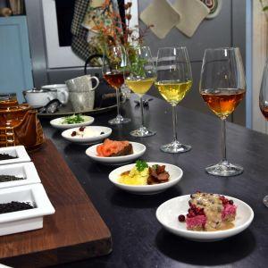 viinilaseja joissa eri teejuomia sekä lautasia joissa eri ruokia.