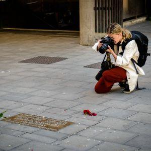 En fotograf tar en bild på Olof Palmes minnesplakett. Några blommor ligger invid plaketten.