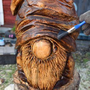 En träskulptur på en tomte som penslas med tjära.