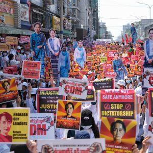 paljon mielenosoittajia, joilla on vallankaappausta vastustavia kylttejä ja Aung Saan Suu Kyin kuvia.