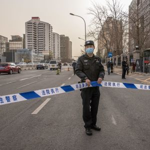 En polis står utanför en domstolsbyggnad i Kina