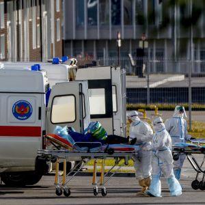 Suojapukuihin pukeutuneet henkilöt siirtävät potilasta paareilla ambulanssista