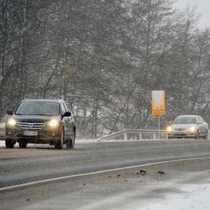Fyra personbilar kör i trafiken. På vägen syns det slask och vid dikeskanten snö.