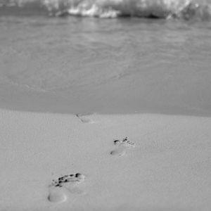 Svartvit bild på fotspår på en stran.