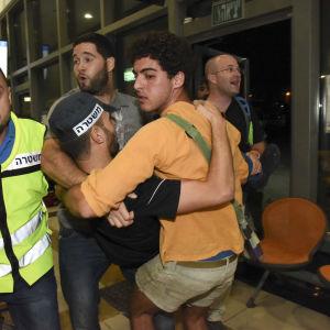 Israeler bär en polis som skadats i en attack på busstationen i staden Beersheba den 18 oktober 2015.