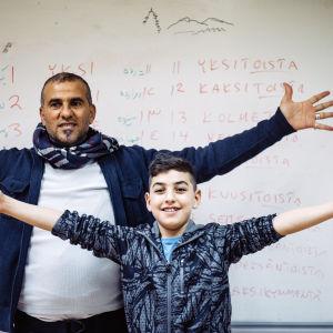 En vuxen man och en pojke står med utsträckta armar framför en skoltavla med finska ord
