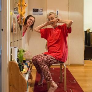 tytär kurkistaa ovesta, äiti etualalla laittaa papiljotteja