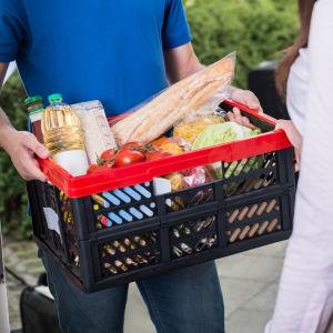 En person levererar en låda med mat till en annan person vid ytterdörren.