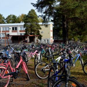 Cyklar parkerade framför skola.