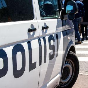 Polisbil står vid ett övergångsställe med människor som går över vägen i bakgrunden.