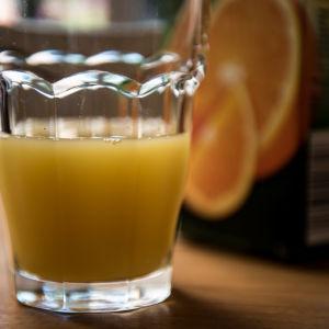 ett glas med gul saft