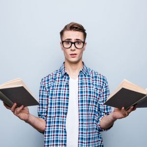 epätoivoinen mies pitää kirjoja kädessään