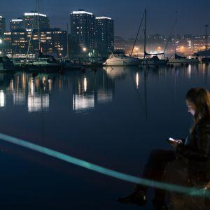 Tyttö istuu illalla satamassa veden äärellä, käyttää puhelintaan