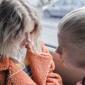 Nuori tyttö bussissa, mies katsoo painostavasti.