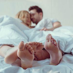 Man och kvinna ligger i en säng med huvudena tätt ihop