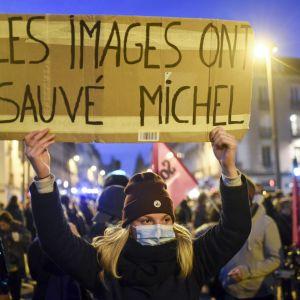 Bilderna räddade Michel, står det på plakatet som en demonstrant höll upp över sitt huvud under en protest mot polisen.