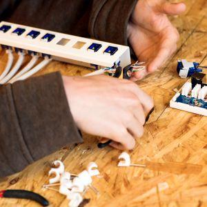 Närbild med en ung persons händer som har en elektrisk dosa framför sig på ett bord och personen använder tång för att knipa av trådar i en elektrisk ledning.
