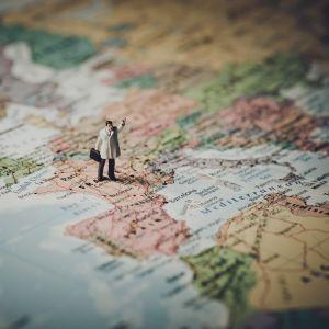 En miniatyr på en man med vit kappa och portfölj står på en karta av Europa och höjer handen.