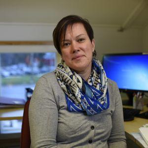 kvinna med scarf sitter framför dator