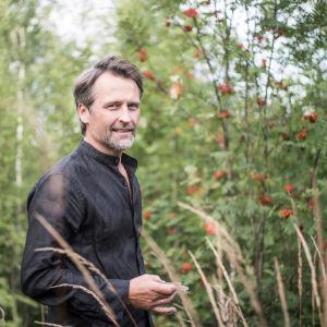 En man i svart läderjacka med grått skägg står i naturen med bland annat röda rönnbär i bakgrunden. Han står snett så att han vänder huvudet mot kameran med ett litet leende på läpparna.