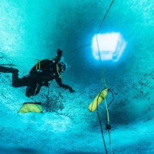 En dykare dyker under isen i Antarktis.