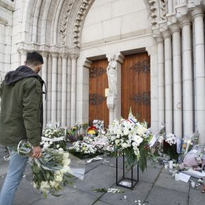 En man lägger en bukett utanför Notre-Dame-basilikan i Nice den 30 oktober 2020 till minne av offren i knivattacken.