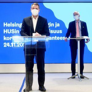 Två män står vid sina podium och håller presskonferens.