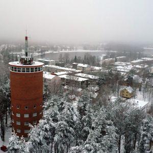 Vanha, punatiilinen vesitorni keskellä lumista mäntymetsää, taustala näkyy Heinolan kaupunki.