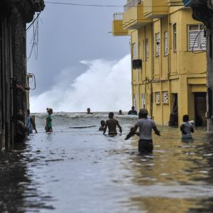 Människor vadar i midjehögt vatten nära paradgatan Malecón i Havanna på söndagen 10.9.2017